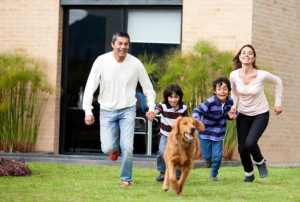Happy family running after a dog outdoors